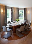 Classic dining room with cantilevered chairs upholstered in gray around an oval table and gray floor length curtains at the window