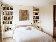 White bedroom with a double bed and built-in shelves with nightstands