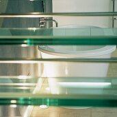 A bathtub behind glass stairs
