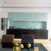 Built in kitchen with glass cabinets and dining table with chair