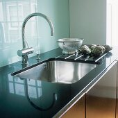 A sink in front of a glass backsplash