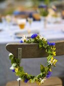 Flower wreath for a midsummer celebration hanging on a chair
