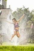 A girl jumping in a sprinkler