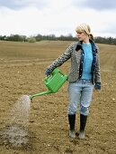 A woman watering a field with a watering can