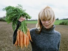 A woman proudly holding freshly harvested carrots