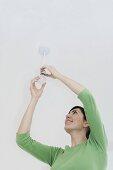 A woman changing a lightbulb