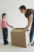A father and daughter taping a box closed