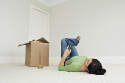 A woman on the phone lying on the floor next to a cardboard box