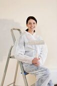 A woman with paint roller sitting on a ladder