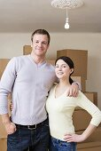 A couple in front of a stack of cardboard boxes