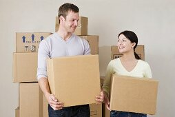 A couple holding cardboard boxes