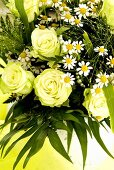 Arrangement of white roses, chamomile flowers and grasses