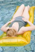 Blond woman lying on an air bed in water