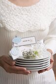 Woman holding pile of plates with Xmas decorations & place cards