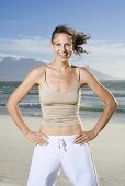 South Africa, Cape Town, Young woman exercising on beach, portrait