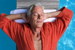 Germany, senior man relaxing on float in pool, close-up, portrait