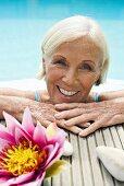 Germany, Senior woman leaning on edge of pool, portrait