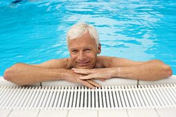 Germany, senior man relaxing in pool, close-up, portrait