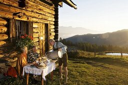 Farmer serving mature couple sitting in front of alpine hut