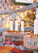 Candleholders made from bricks holding three white candles and decorated with leaves & berries