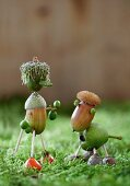 Dog and owner crafted from acorns, thistles and acorn cups