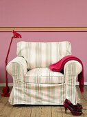 Armchair with striped cover and red metal standard lamp against pink wall