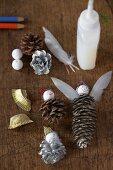 Weihnachtliches Bastelmaterial - Tannenzapfen, Federn, Klebstoff und Kugeln auf Holzablage