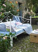 Rose-patterned cushions and blankets in shades of blue on metal-framed day bed in garden
