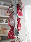 Red and white advent calendar sacks handing on a metal chain