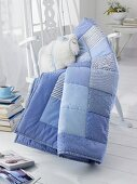 A blue patchwork blanket and a homemade cuddly toy sheep on a rocking chair
