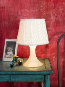 Table lamp with knitted lampshade on blue side table