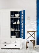 Open cupboard with blue and white striped wallpaper on back wall