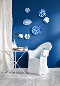 Small dining area with folding table and chair with loose cover against wall with blue wallpaper and blue and white decorative wall plates