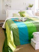 Doppelbett mit gestreiften Bettüberwurf in verschiedenen Grüntönen