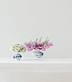 Two posies of daisies and sweet peas on white table