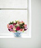 Bouquet of garden roses in vase on window sill