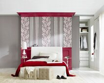 Bedroom in grey and red, wallpaper with pattern of paisley and stripes behind bed