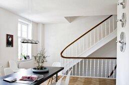 Wohnraum mit Esstisch neben Treppenaufgang