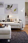 Wohnzimmer in hellen Farbtönen mit Sofa, Stehlampe & Wandbildern