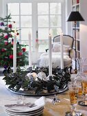 An advent wreath with silver Christmas decorations and white candles on a table