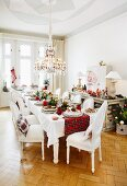 A land-house style table laid for Christmas dinner with a tartan table runner