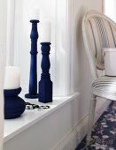 Blue candlesticks made from table legs on windowsill