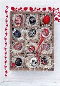 Red and black, hand-painted Easter eggs in a seedling tray lined with straw