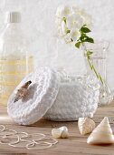 A white crocheted container with seashells