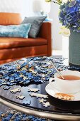 Jigsaw pieces and cup of tea on coffee table with leather couch in background