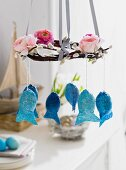 A homemade catkin wreath decorated with flowers and fish-shaped Easter eggs
