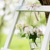 Vases of apple blossom and daisies hanging from ladder