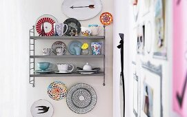 Various collector's cup on a metal shelf on a kitchen wall