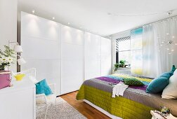 Bedroom with fitted wardrobes & double bed with colourful quilted bedspread