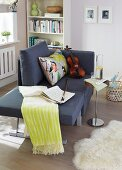 An armchair that folds out into a recamier with floral-patterned cushions and a fringed blanket creating a cosy corner in a living room